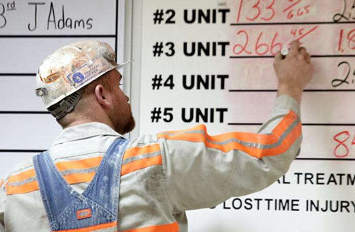 An Alliance Resource Partners employee writes down data on a whiteboard.