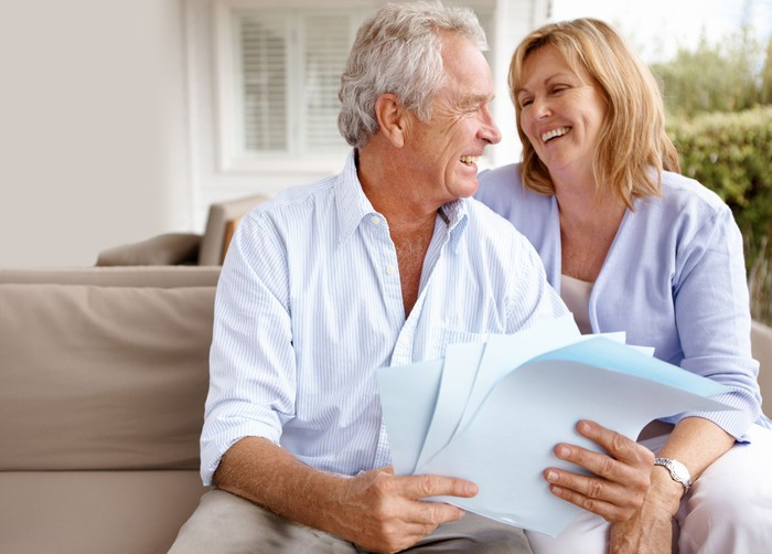 Mature couple smiling while reviewing papers