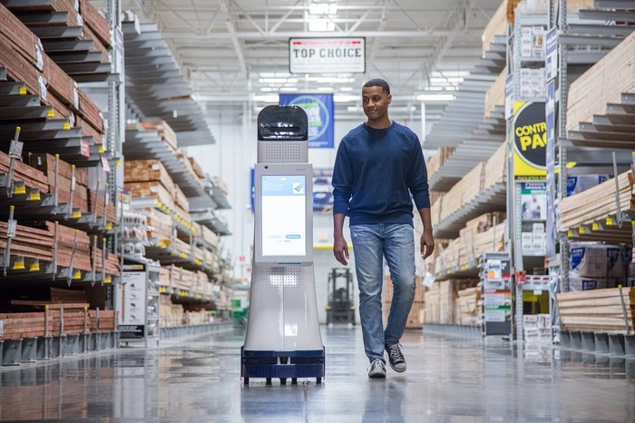 A LoweBot with a shopper walking alongside it. LoweBots look like a rolling aisle display, but have a touch screen on their front for shoppers to interact with them.