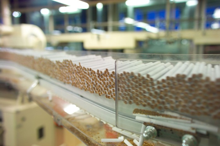 Stacks of cigarettes roll down an assembly line.