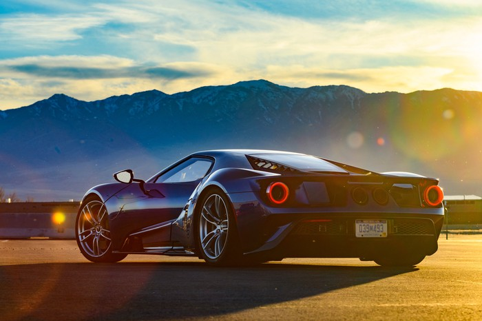 The rear view of a Ford GT, with mountains and the sun in the background.