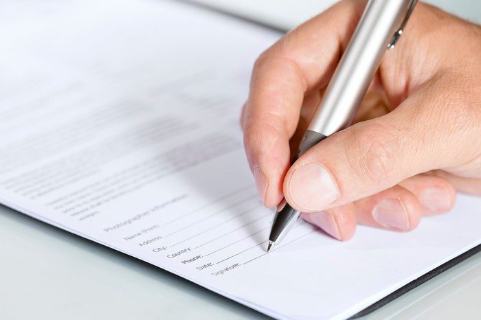 Close-up of hand signing document.