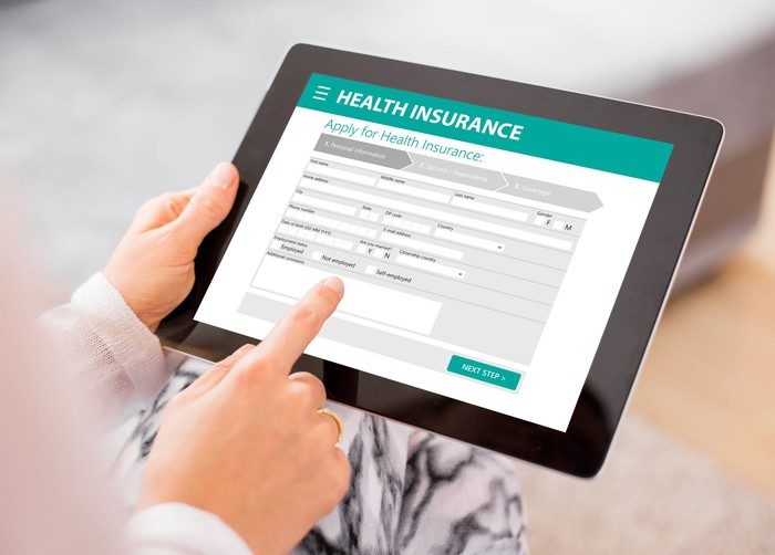 Woman completing health insurance application on tablet.