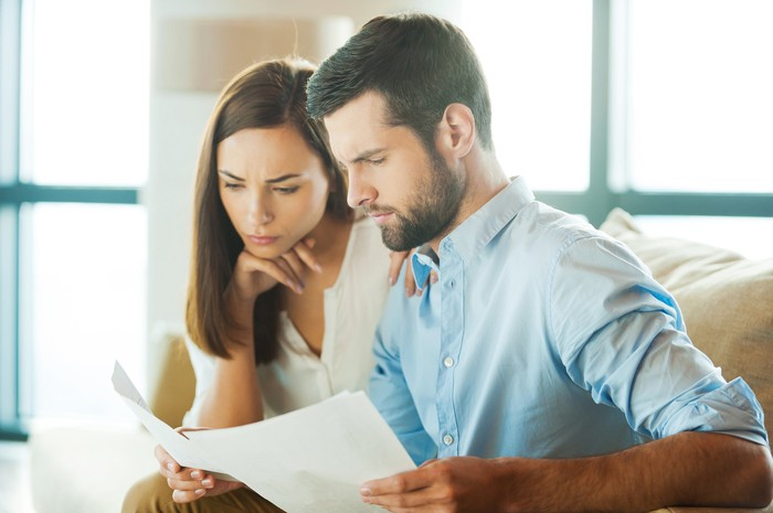 Young couple looking at document.