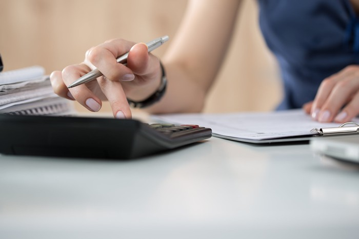 A woman with a pen in her hand uses a calculator.