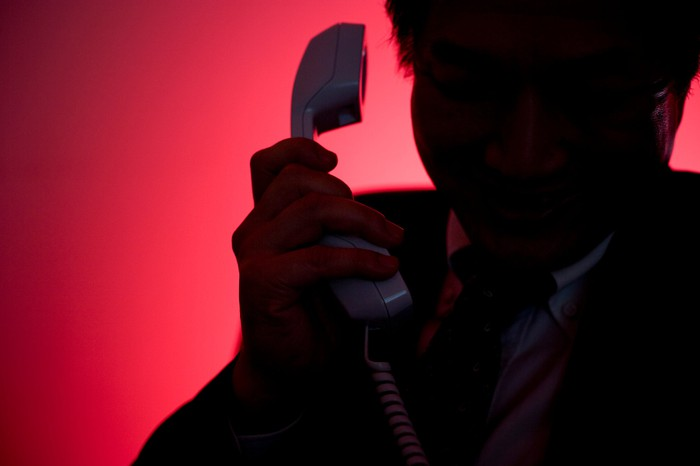 A man silhouetted against a red background raises a phone to his ear.