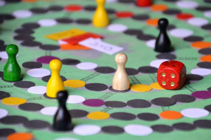 Several colorful pawns and a red die are positioned on a game board.