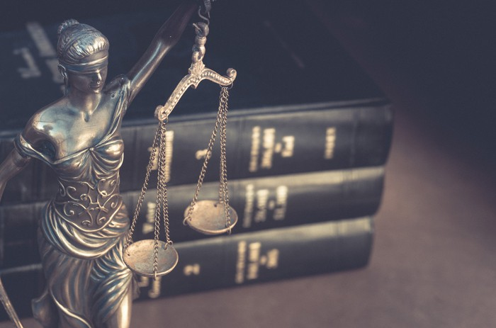 A statue of Justice stands before a stack of law books.
