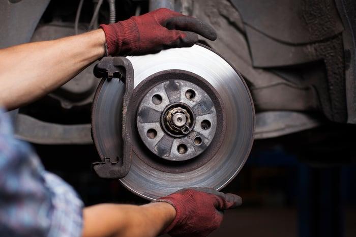 Mechanic fixing brakes on a car