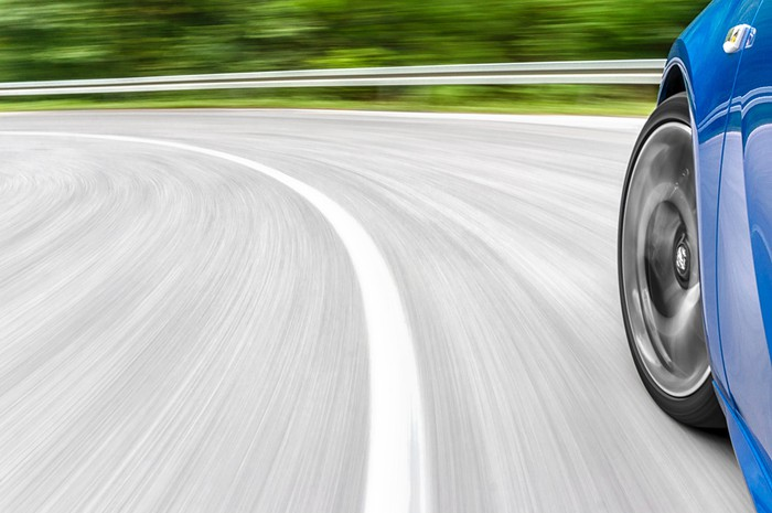 Motion blur shot of  a car driving fast on the road, showing the front corner of the car from a side view.