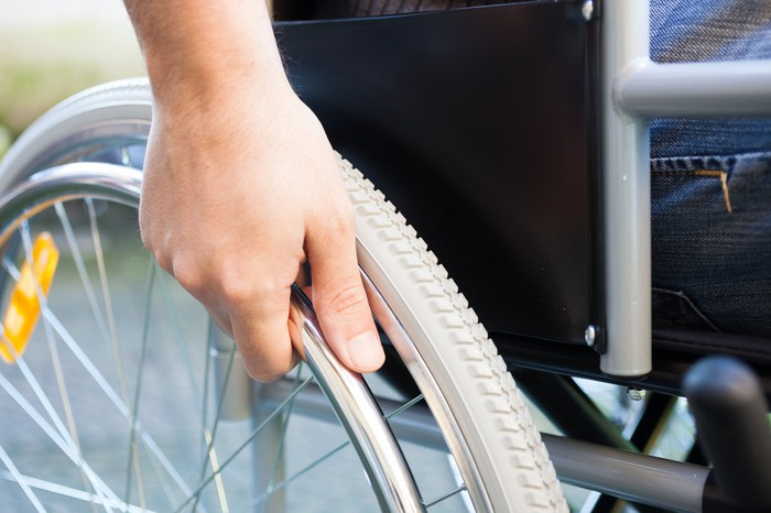 A person in a wheelchair places his hand on the wheel.