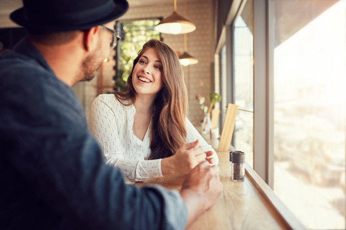 A smiling young woman sits in a cafe, talking to a man.