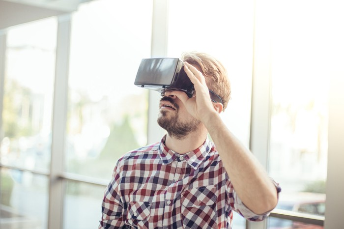 A young man uses a virtual reality headset.