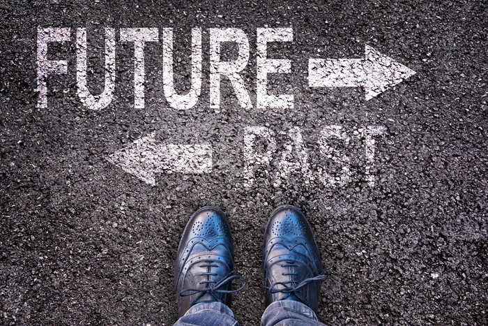 One arrow points to the future, while one points the opposite directions to the past, with feet perpendicular.