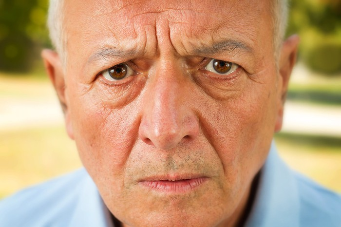 An older man looks at the camera with an annoyed expression.