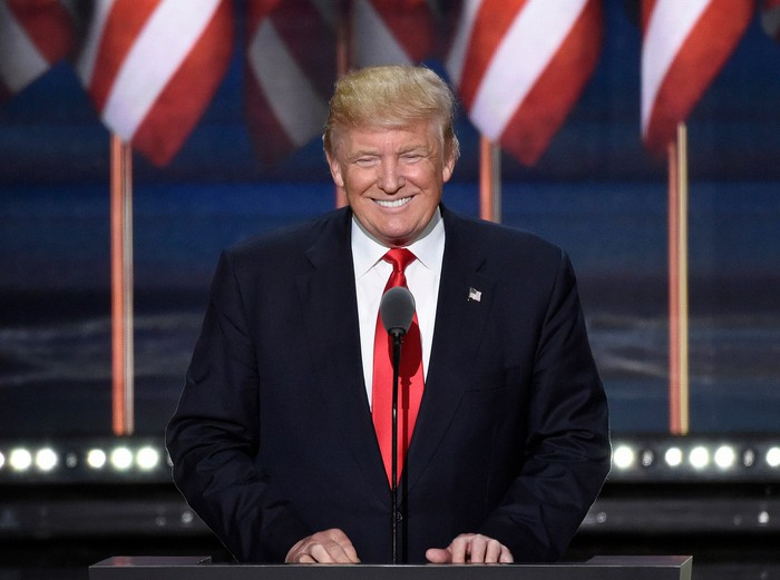 President Donald Trump smiling at podium.