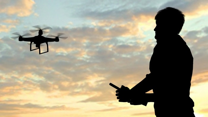 Man flying a drone quadrocopter at sunset.