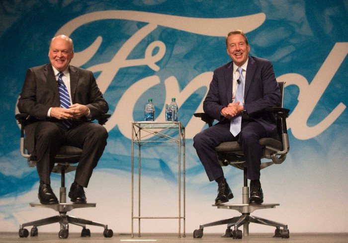 Jim Hackett and Bill Ford seated on a stage in front of the Ford logo
