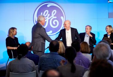 New GE CEO John Flannery shakes hands at a gathering.