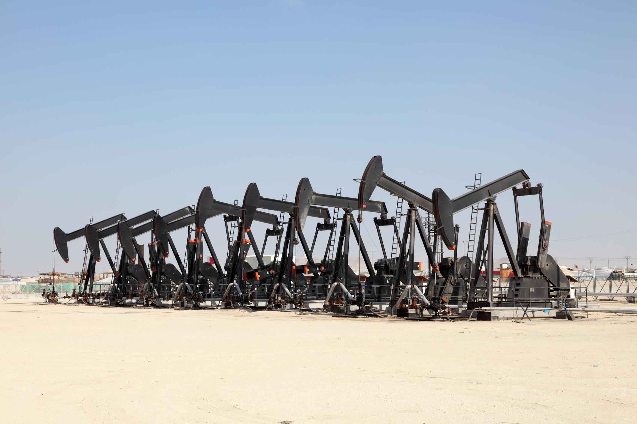 Black oil pump jacks in the desert.