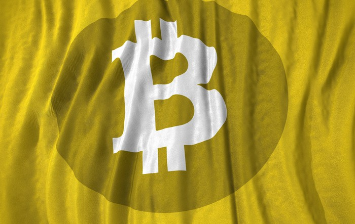 Bitcoin currency symbol on a yellow backdrop.