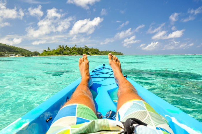 Man wearing board shorts sitting on the ocean with islands in the background.