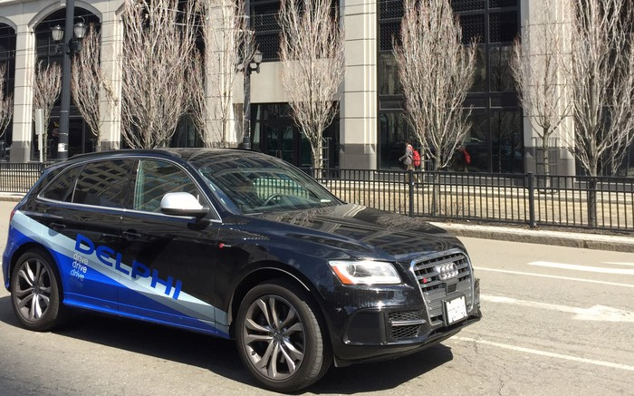 """A black Audi SUV with self-driving sensors and """"Delphi"""" graphics."""