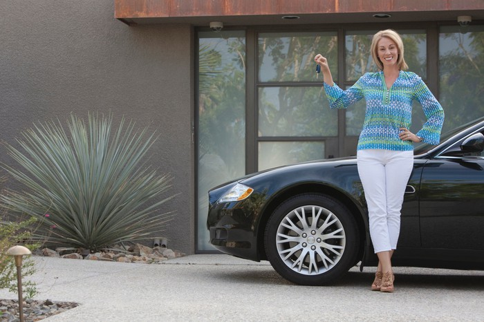 A smiling woman holds up a set of car keys as she stands next to a parked car.