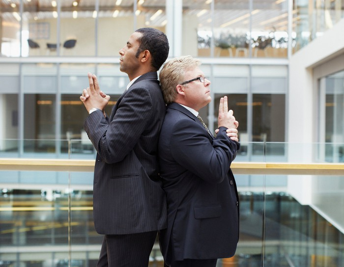 Businessmen back to back fighting symbolic duel with fingers raised as weapons.