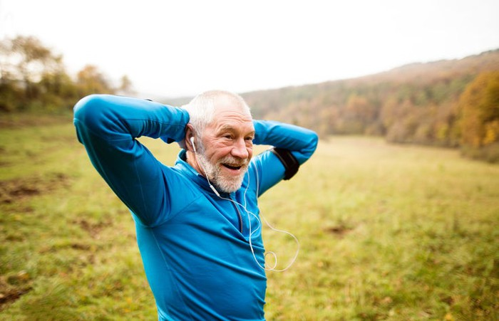 A senior citizen taking a break from a run in an open field.