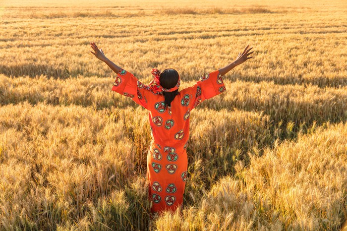 An indigenous woman with arms raised triumphantly toward an open field.