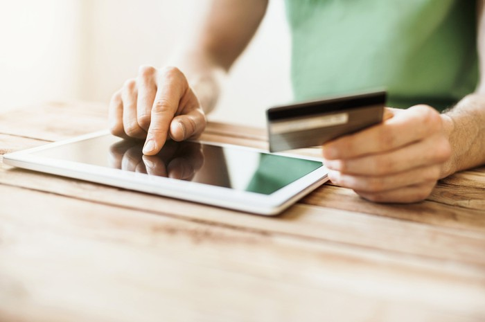 Man buying something on a tablet, holding a credit card.