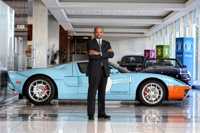 Nair is standing in front of a Ford GT sports car.