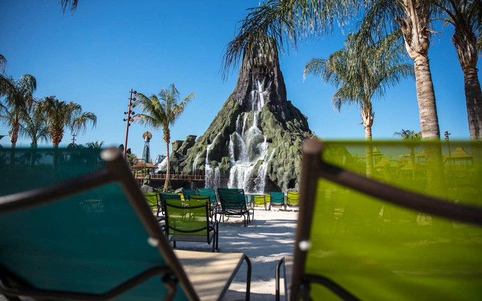 Beach shot of Volcano Bay's signature volcano with a waterfall trickling into the wave pool.