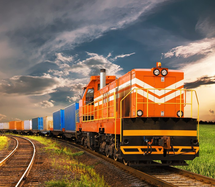 A freight train with cars of various colors sits on a track, with a cloudy sky in the background.