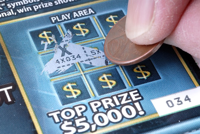 Person playing a scratch-off lottery game.