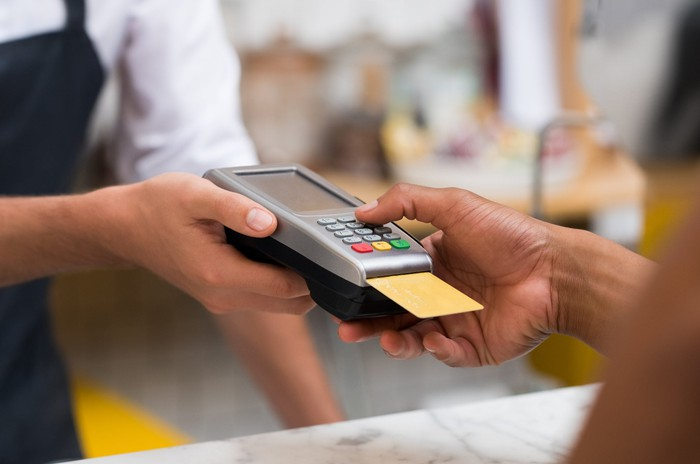 A merchant holds a credit card machine for a customer, who presses a key with his card inserted.