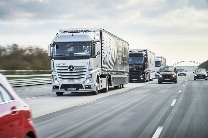 Three Mercedes-Benz tractor-trailers in close formation on the highway. The human driver of the lead truck is not touching the steering wheel.