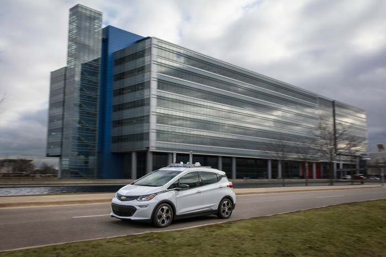 A white Chevrolet Bolt EV with autonomous-vehicle sensors is shown driving past GM's Technical Center in Warren, Michigan.
