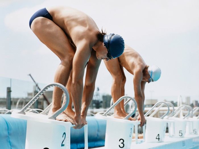 Two Men Standing Side by Side on Starting Blocks at a Swimming Pool.