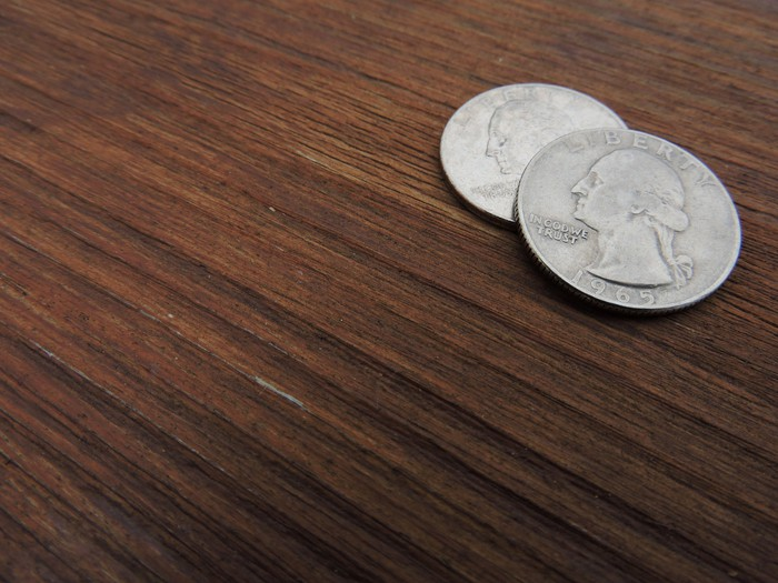 Two quarters sitting on a table.