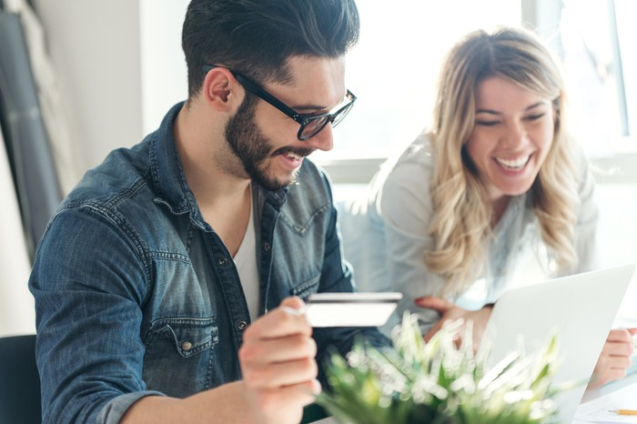 A smiling couple shops online with a credit card.