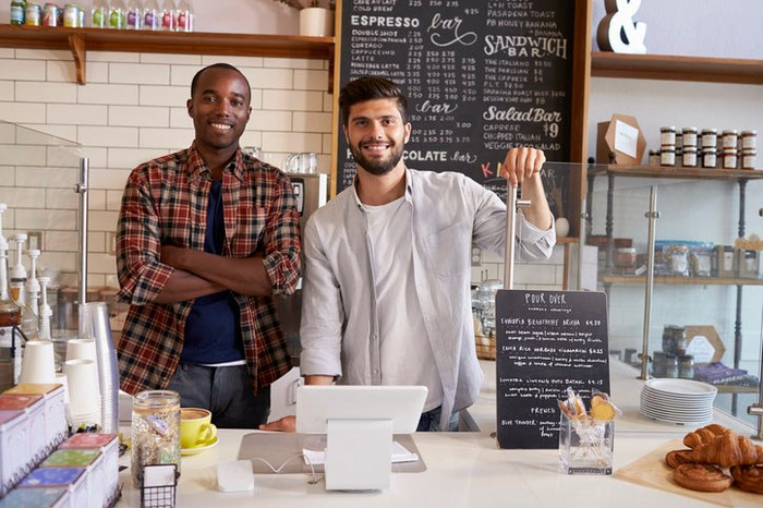 Two young males smiling inside their coffee shop business.