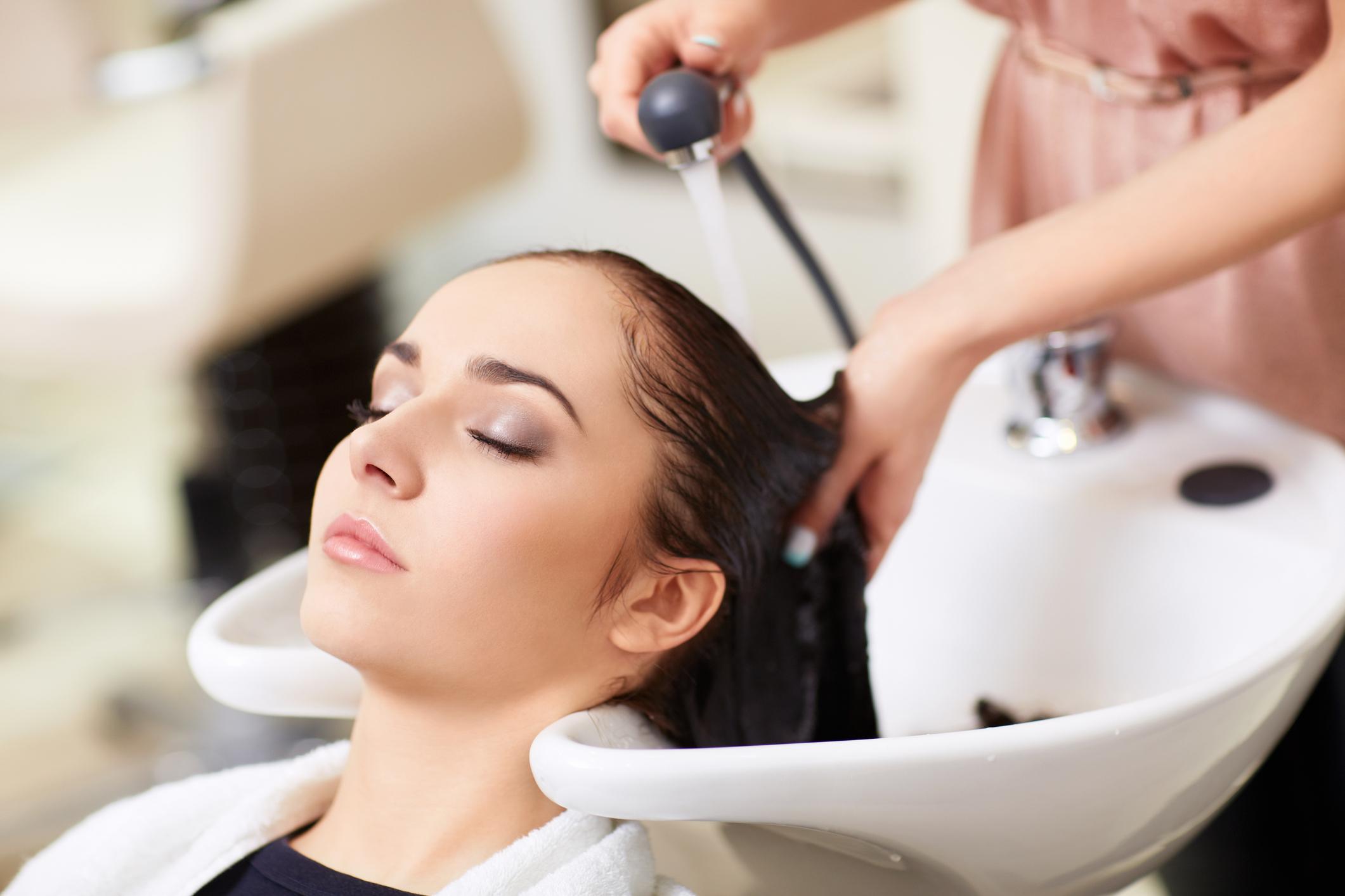 A woman receives a hair treatment at a spa.