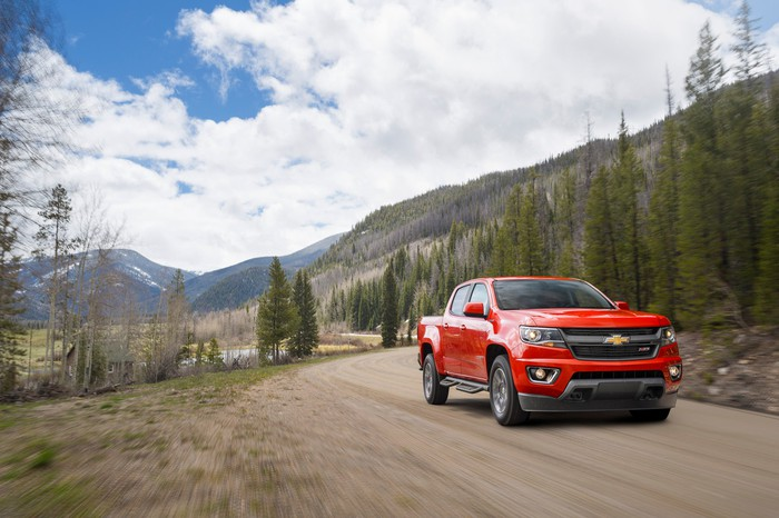 Red Chevrolet Colorado driving on a mountain road.