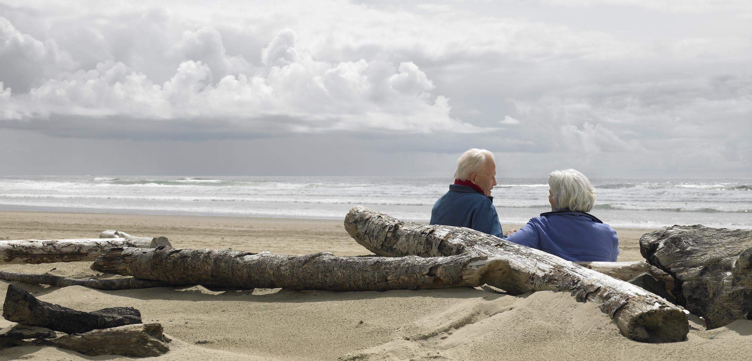 Retired couple sitting on beach.