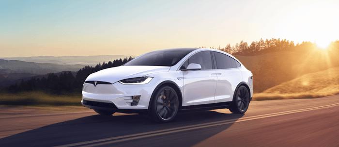 Tesla Model X speeding out of a sunset.