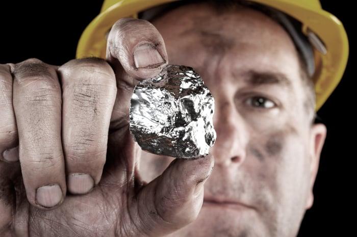 A man holding a silver rock.