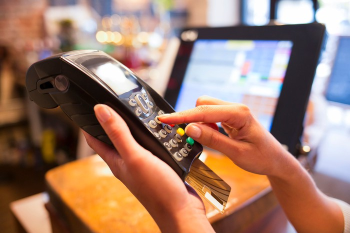 Cashier ringing up a credit card transaction on a handheld credit processing device.