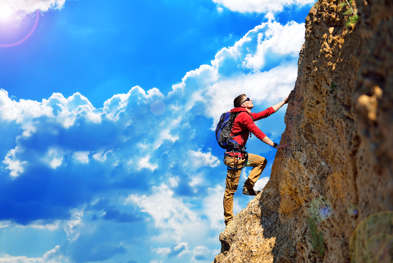 Mountain climber scaling a rock face.